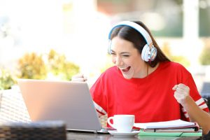 Female on computer with headphones